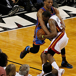 Jun 19, 2012; Miami, FL, USA; Oklahoma City Thunder point guard Russell Westbrook (0) fouls Miami Heat point guard Mario Chalmers (15) during the fourth quarter in game four in the 2012 NBA Finals at the American Airlines Arena. Miami won 104-98. Mandatory Credit: Derick E. Hingle-US PRESSWIRE