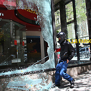 A black-clad protester smashes windows on a Wells Fargo branch during a May Day rally on Tuesday, May 1, 2012 in downtown Seattle. (Joshua Trujillo, seattlepi.com)