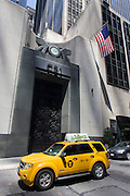 A hybrid taxi cab passes the tall doorway of the East River Savings Bank in Lower Manhattan, New York City.