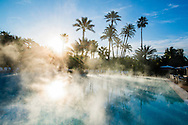 Sunrise over tropical swimming pool. Rising steam catches the morning sun.