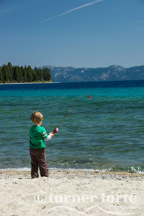 Toddler boy pretends with fishing pole and toy fish on the shores of Meeks Bay, Lake Tahoe, California.
