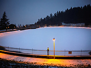 Fresh snow on frozen-over Reservoir 5, Mount Tabor Park, Portland, Oregon, USA.