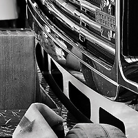 A black and white image of the front grill and bumper of a fire engine parked in the Vienna Volunteer Fire Department firehouse, Vienna, Virginia.