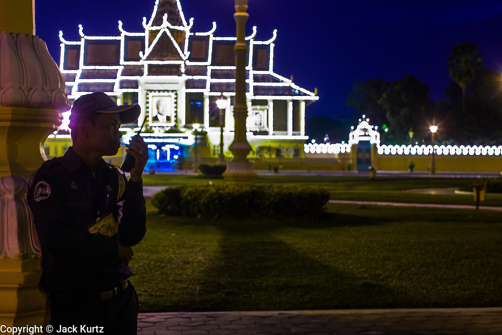 02 FEBRUARY 2013 - PHNOM PENH, CAMBODIA:  A Cambodian police officer is silhouetted by the lights of the Royal Palace in Phnom Penh. Much of Phnom Penh has been shut down to honor former King Norodom Sihanouk, who ruled Cambodia from independence in 1953 until he was overthrown by a military coup in 1970. Only bars, restaurants and hotels that cater to foreign tourists are supposed to be open. The only music being played publicly is classical Khmer music. Sihanouk died in Beijing, China, in October 2012 and will be cremated during a state funeral royal ceremony on Monday, Feb. 4.    PHOTO BY JACK KURTZ