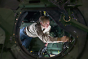 A worker installs electronics on a military Hummer before being shipped to Iraq.
