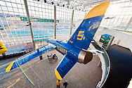 Grumman F11(F-11) Tiger jet seen from above, with natural Sun Flare giving illusion of wing motion, suspended from Cradle of Aviation museum ceiling. &quot;U.S. NAVY&quot; printed in yellow on blue plane. Ultra wide angle view of 3 floor atrium lobby.<br />
