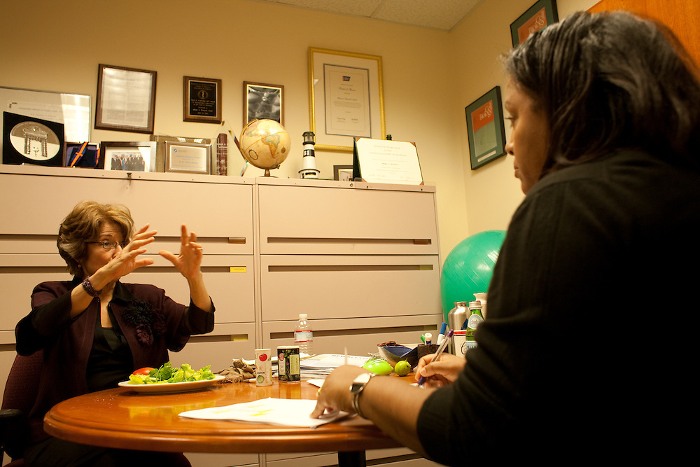 Dr. Bissell eats lunch in her office while dictating a memo to her senior administrator Negest Williams, on December 18, 2009.