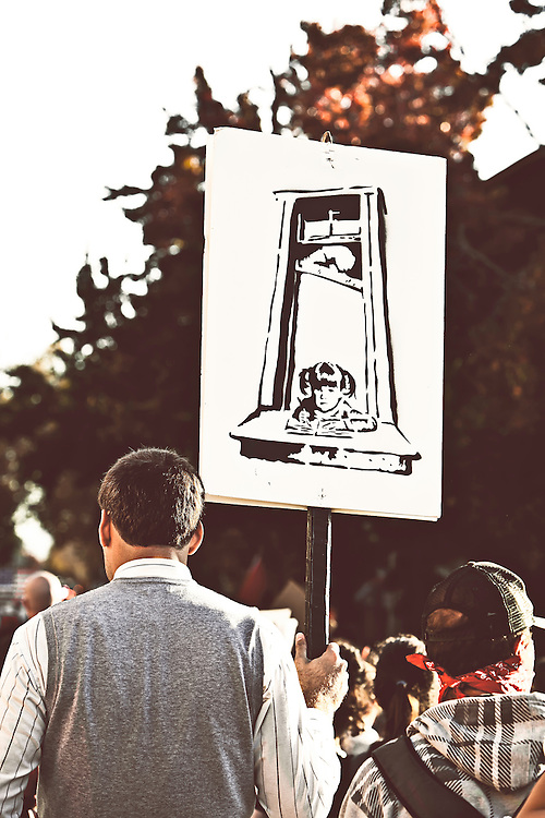 Man carries visually gripping sign at Occupy Berkeley movement in Berkeley, CA.  Copyright 2011 Reid McNally.
