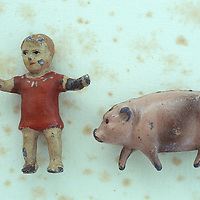 Worn lead models of Victorian toddler with arms outstretched and jaunty plump pig lying on antique paper