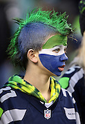 A young fan sports a painted face and a team colored mohawk haircut during the Seattle Seahawks NFL week 19 NFC Divisional Playoff football game against the Carolina Panthers on Saturday, Jan. 10, 2015 in Seattle. The Seahawks won the game 31-17. ©Paul Anthony Spinelli