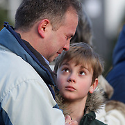 A man, watched by a young boy, cries at the shrine created under the school sign in Sandy Hook after yesterday's shootings at Sandy Hook Elementary School, Newtown, Connecticut, USA. 15th December 2012. Photo Tim Clayton