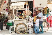 A Mexican grilled corn vendor selling elotes from a traditional cart in Dolores Hidalgo, Guanajuato, Mexico. The town is where Independence leader Miguel Hidalgo issued the now world famous Grito - a call to arms for Mexican independence from Spain.