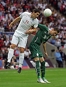 Gareth Barry outjumps Milivoje Novakovic during the international friendly match between England and Slovenia at Wembley Stadium, London on the 5th September 2009