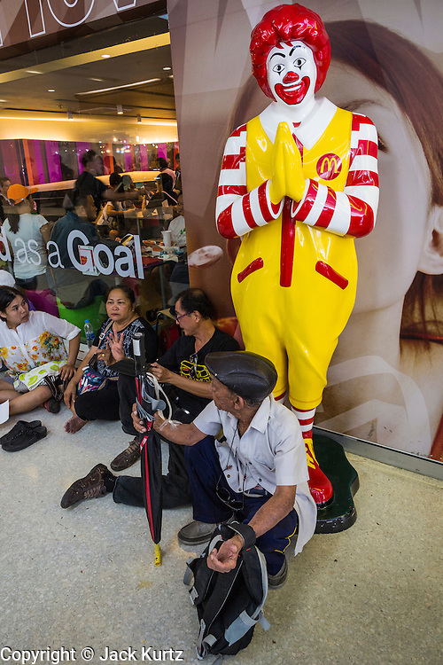 25 MAY 2014 - BANGKOK, THAILAND: Thai anti-coup protestors relax in front of a McDonald's in a Bangkok shopping mall. Public opposition to the military coup in Thailand grew Sunday with thousands of protestors gathering at locations throughout Bangkok to call for a return of civilian rule and end to the military junta.     PHOTO BY JACK KURTZ