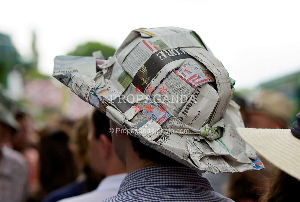 LONDON, ENGLAND - Monday, June 23, 2014: A spectator fashions a hat out of newspaper during day one of the Wimbledon Lawn Tennis Championships at the All England Lawn Tennis and Croquet Club. (Pic by David Rawcliffe/Propaganda)