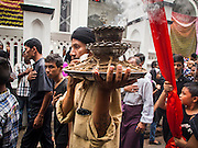 04 NOVEMBER 2014 - YANGON, MYANMAR: Burmese Shia Muslims in Yangon participate in a procession for Ashura. Ashura, commemorates the death of Hussein ibn Ali, the grandson of the Prophet Muhammed, in the 7th century. Hussein ibn Ali is considered by Shia Muslims to be the third imam and the rightful successor of Muhammed. He was killed at the Battle of Karbala in 610 CE on the 10th day of Muharram, the first month of the Islamic calendar. According to Myanmar government statistics, only about 4% of the population is Muslim. Many Muslims have fled Myanmar in recent years because of violence directed against Burmese Muslims by Buddhist nationalists.     PHOTO BY JACK KURTZ