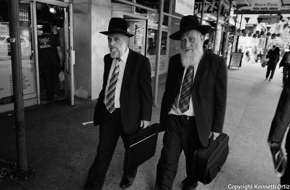 Two Hasidic business men walking down a New York City Street.
