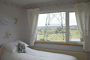 An electricity pylon is seen through a bedroom window where a pillow