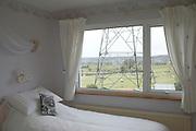 An electricity pylon is seen through a bedroom window where a pillow