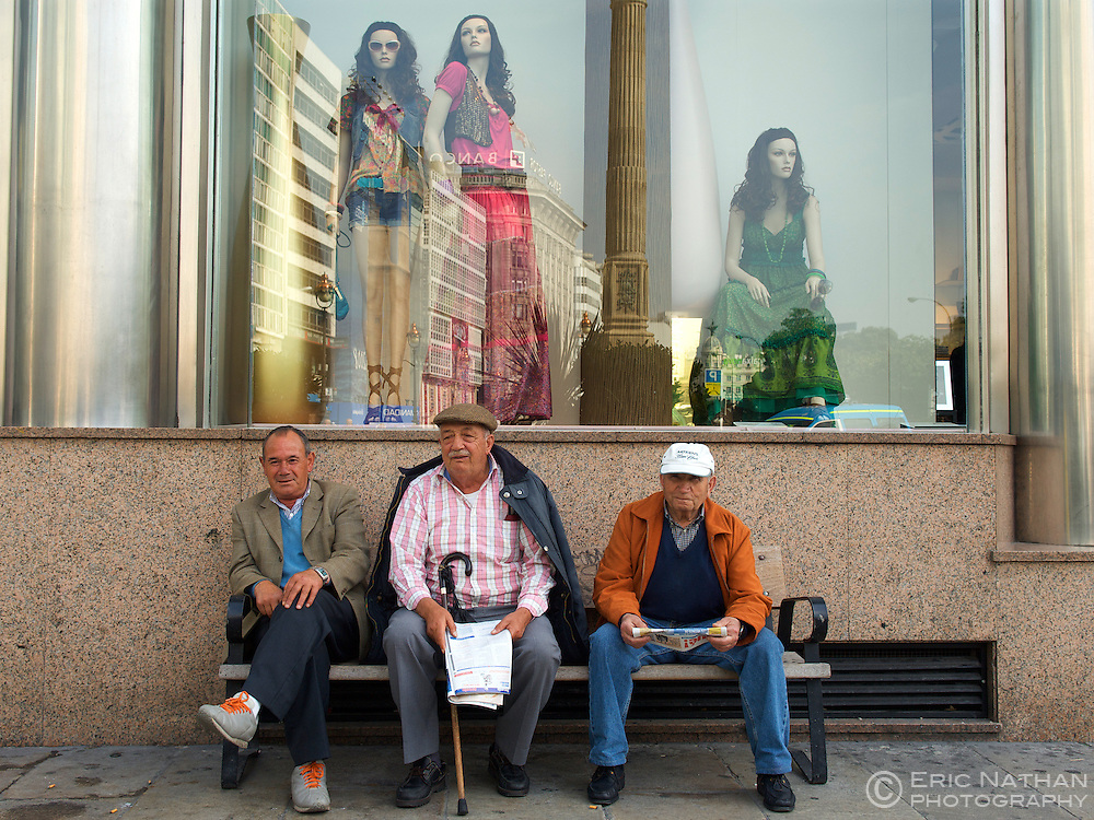 Three Spanish men sitting on a bench in the town of La Coruña in the Galicia region of Spain.