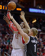 Nov 29, 2013; Houston, TX, USA; Houston Rockets power forward Dwight Howard (12) shoots against Brooklyn Nets power forward Mason Plumlee (1) during the first quarter at Toyota Center. Mandatory Credit: Thomas Campbell-USA TODAY Sports