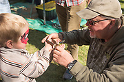 Gentleman handing a snake to a little boy at the Thousand Springs Art Festival at Ritter Island near Hagerman, Idaho.