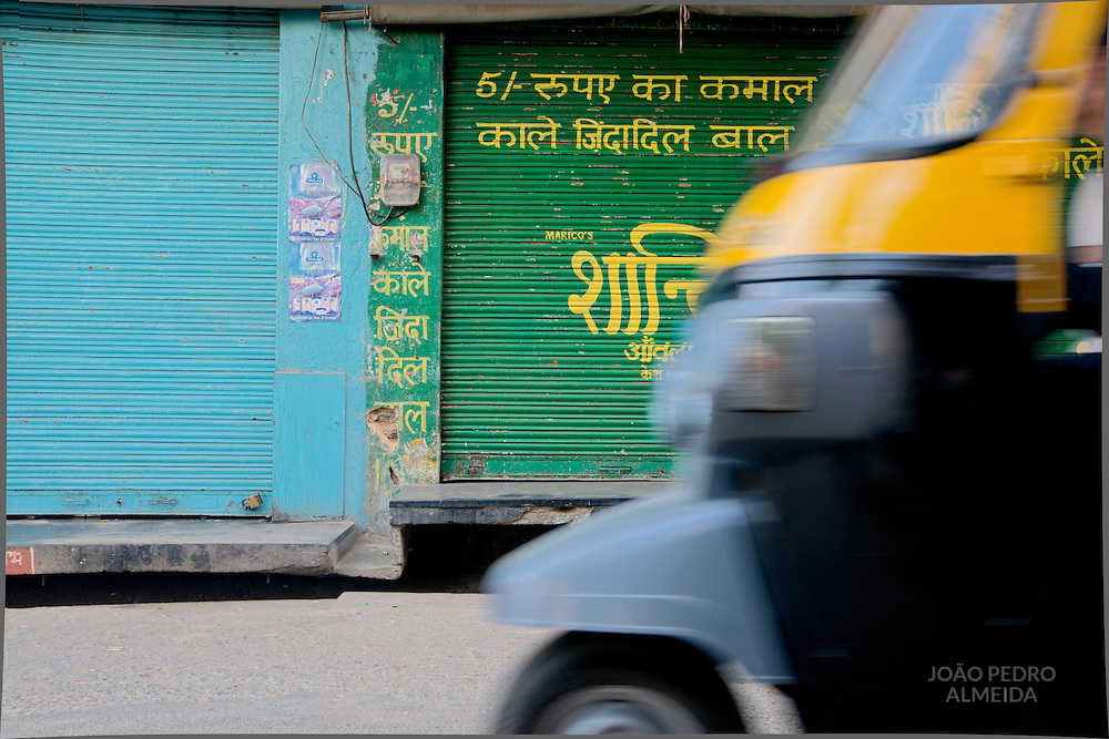 Autorickshaw passing by closed shop at Udaipur