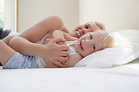 Mother embracing daughter (3-4) in bed smiling