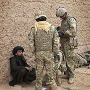 British soldiers of 16 Air Assault Bde's elite BRF (Brigade Reconnaissance Force) use an interpreter to question a local man as they move from compound to compound searching for weapons and explosives as part of an operation in the Western Dasht, Helmand Province, Southern Afghanistan on the 18th of March 2011.