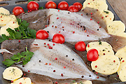 Baking tray with raw turbot fish and sliced potatoes, seasoned with black and red pepper, cherry tomatoes and parsley, ready to be baked.