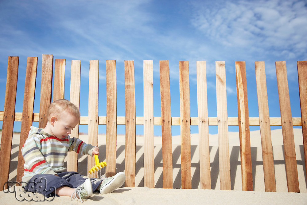 Boy (1-2) playing with beach rake by wooden fence on sand dune