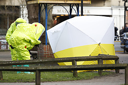 © Licensed to London News Pictures. 08/03/2018. Salisbury, UK. Salisbury. Officials in hazardous material suits adjust a police tent covering a park bench next to Maltings shopping centre in Salisbury where Former Russian spy Sergei Skripaland his daughter Yulia were found after being poisoned with nerve agent. The couple where found unconscious on bench in Salisbury shopping centre. Authorities continue to investigate. Photo credit: Peter Macdiarmid/LNP