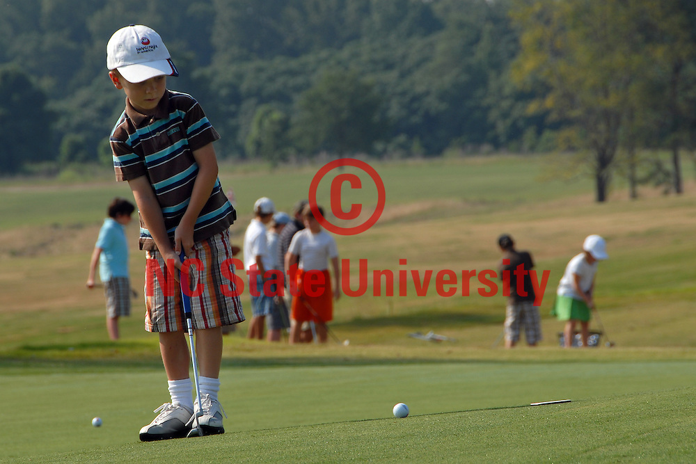 Golf camper works on his putting skills at the Lonnie Poole Golf Course. PHOTO BY ROGER WINSTEAD