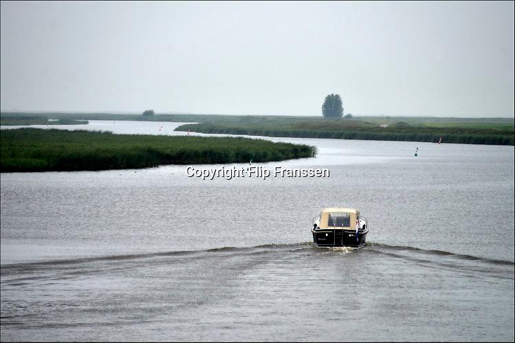 Nederland, Zoutkamp, 11-8-2016Een plezierjacht vaart het lauwersmeer op vanuit de sluis bij Zoutkamp, voormalig vissersdorp gelegen aan de monding van het Reitdiep . Voor de indamming een openverbinding met de Waddenzee, de Lauwerszee . In Zoutkamp bevindt zich een jachthaven van waaruit veel pleziervaartuigen een tocht maken .Nationaal Park Lauwersmeer, een natuurgebied op de grens van Groningen en Friesland. Het is een natuurgebied dat ontstond na de indamming van de Lauwerszee in 1969 waarbij het gebied werd afgescheiden van de Waddenzee en zoetwatergebied werd. Het Lauwersmeer is  onderdeel van de Ecologische Hoofdstructuur . Foto: Flip Franssen