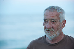 Older man looking towards the ocean at dusk