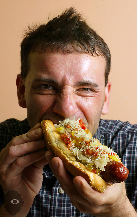 Steve Yazzolino of JAVADOGS munches down on his vaorite double smoked sausage dog. It is garnished with relish, onion, sauerkraut, pepperocini, tomato, cucumber, fennel salt and parmesian cheese...