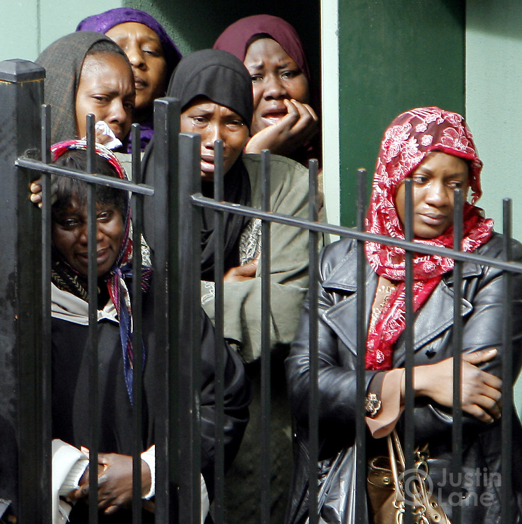 Women weep while watching the coffins of the ten people killed in a recent house fire arrive for funeral services at the Islamic Cultural Center in the Bronx, New York on Monday 12 March 2007. Of the ten people killed in the fire, 9 were children, and all were immigrants from Mali.