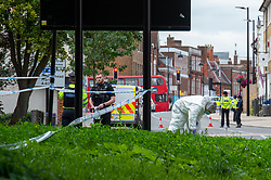 © Licensed to London News Pictures. 07/09/2020. High Wycombe, UK. A forensic investigator searching for evidence in a grassy area on a traffic island after reports of a stabbing on Easton Street in High Wycombe, a large cordon centred around the High Wycombe Magistrates Court. Photo credit: Peter Manning/LNP
