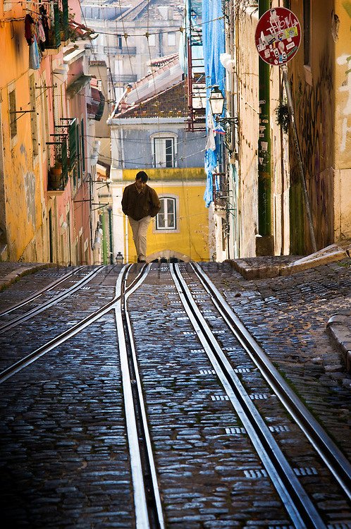 A man walking through the streets of the Barrio Alto in Lisbon