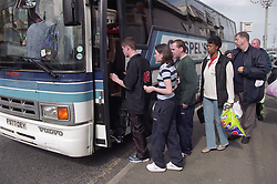 Group of people standing in line waiting to climb aboard coach,