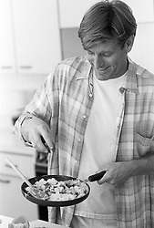 Man in a kitchen holding a skillet making an omelette
