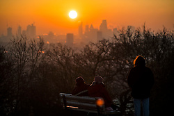 © Licensed to London News Pictures. 12/12/2017. London, UK. A group of young women watch the sun rise over the city of London from Hampstead Heath in north London on a freezing morning. Temperatures across the the UK dipped overnight with some regions expected to drop to -13C (9F). Photo credit: Ben Cawthra/LNP