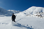 Man walking through thick powder in snowy mountain landscape near Col de Pause, Ariege, Pyrenees, France.