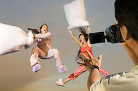 Man video recording two playful women in sleepwear having a pillow fight