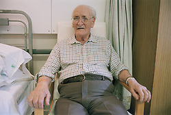 Elderly man sitting next to a bed in Intermediate Care Project,