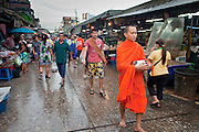 Sept. 23, 2009 -- BANGKOK, THAILAND: A Buddhist monk solicits alms in Khlong Toey Market in Bangkok, Thailand. Khlong Toey Market is the largest market in Bangkok. Vendors sell everything from meat and fish to fruit and vegetables. They also sell clothes and dry goods in the market. Many working class Thais shop for food everyday because they don't have refrigerators and can't store food at home.   Photo by Jack Kurtz
