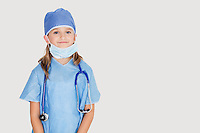 Portrait of young girl in surgeon's costume against gray background
