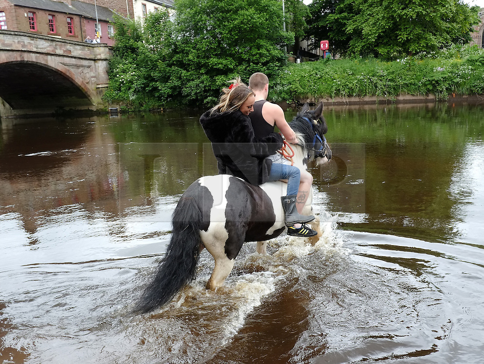 © Licensed to London News Pictures. <br /> 05/06/2014. <br /> <br /> Appleby, Cumbria, England<br /> <br /> The first horse enters the River Eden as gypsies and travellers gather during the annual horse fair on 5 June, 2014 in Appleby, Cumbria. The event remains one of the largest and oldest events in Europe and gives the opportunity for travelling communities to meet friends, celebrate their music, folklore and to buy and sell horses.<br /> <br /> The event has existed under the protection of a charter granted by King James II in 1685 and it remains the most important event in the gypsy and traveller calendar.<br /> <br /> Photo credit : Ian Forsyth/LNP