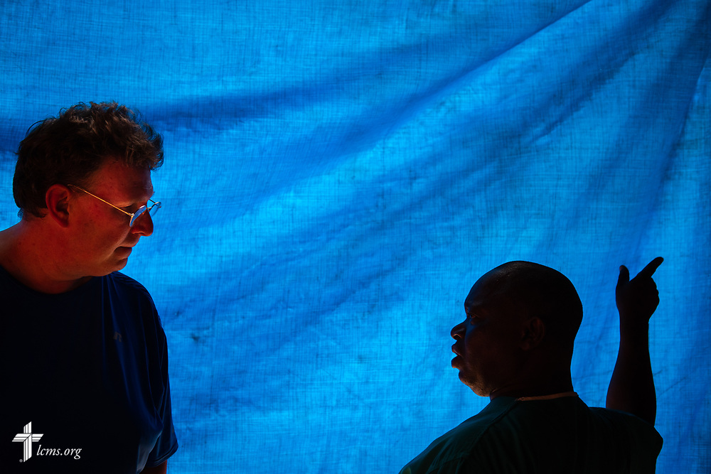 Sierra Leonean nurse and pastor Stephen Ngaujah works with the Rev. Michael Awe, team leader and pastor at Hope Lutheran Church, South Sioux City, Neb., in the pharmacy area of the clinic during the second day of the LCMS Mercy Medical Team on Tuesday, May 8, 2018, in the Yardu village outside Koidu, Sierra Leone, West Africa. The blue tarp helped keep the sun from the pharmacy area. LCMS Communications/Erik M. Lunsford