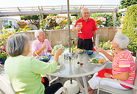 Two mature couples celebrating with a toast around an outdoor patio table under and umbrella..Model Releases.20070822_MR_A.20070822_MR_B.20070822_MR_C.20070822_MR_D.20070822_PR_A